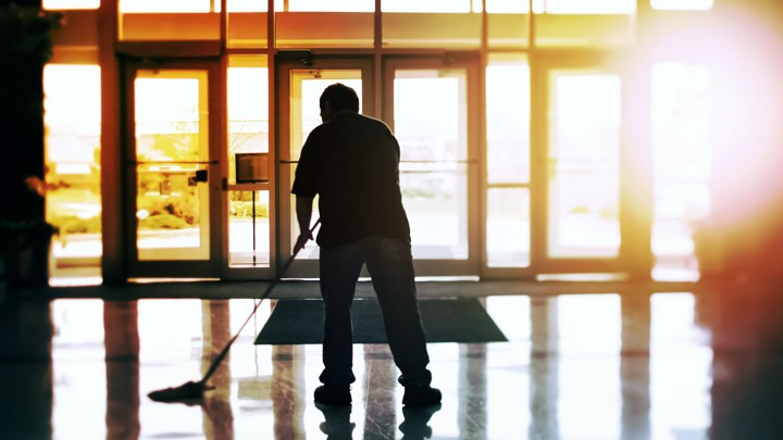 A custodian mops a floor in an office building at sunset.