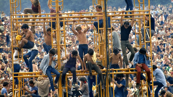 Woodstock attendees sitting on the sound tower.