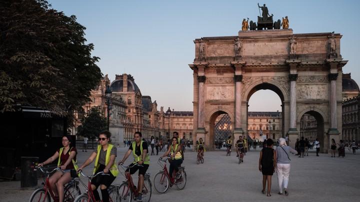 Cyclists stream past the Arc de Triomphe du Carrousel in Paris.