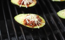 Avocados stuffed with chili sit on a grill.