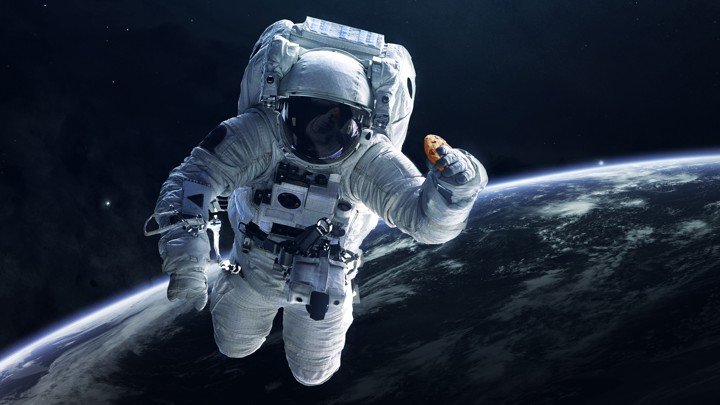 An illustration of an astronaut in space with a chocolate-chip cookie in hand
