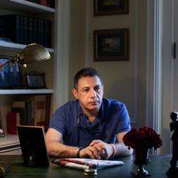 Nizar Zaka sits at a desk, facing past the camera.