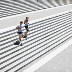 A man and woman jog down cement stairs together.