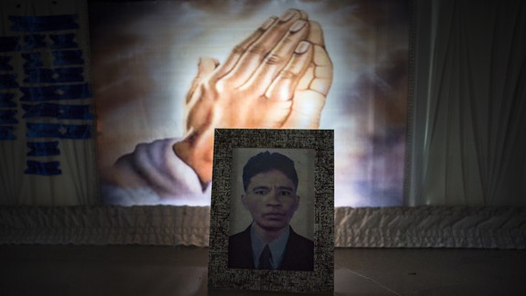 A framed photograph of the victim of a shooting in Manila lies atop his casket.
