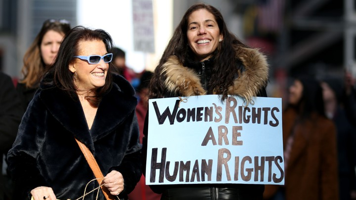 Two women hold placards in a women's rights march in New York City.