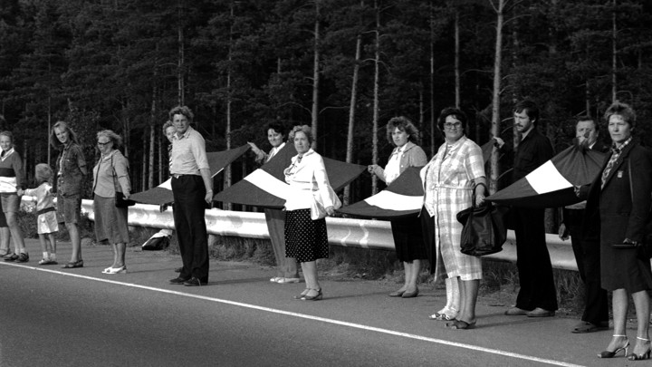 A group of people stand in a line holding hands with Latvian flags.