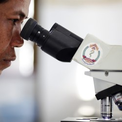 A Cambodian technician uses a normal microscope.