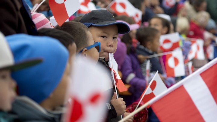 Children holding Greenland's national flag