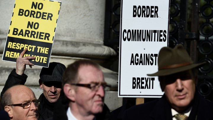 "Four protestors hold signs reading, ""No Border No Barrier, Respect the Remain Vote"" and ""Border Communities Against Brexit."""