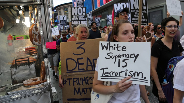 "A protester in a march holds a sign reading ""White supremacy is terrorism."""