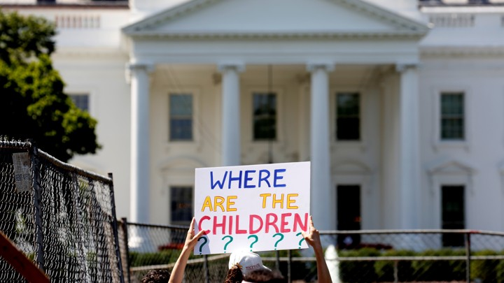 "A protester holding a sign that reads ""Where are the children?"" in front of the White House."