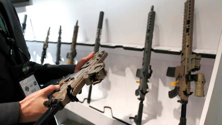 A man looks at a semi-automatic rifle during a gun show in Las Vegas.