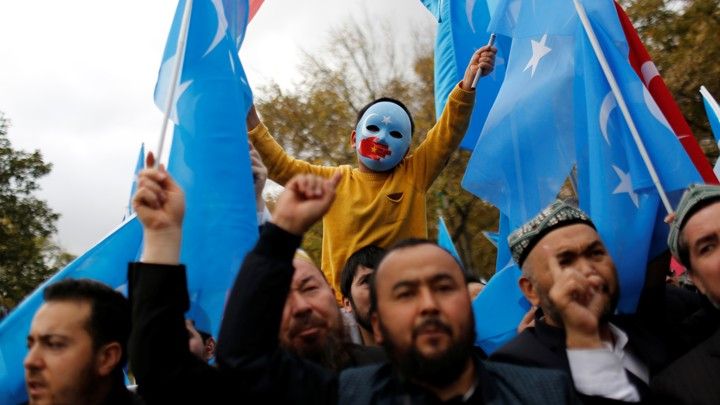 A boy in a blue mask raises two East Turkestan flags in a march.