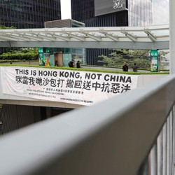 """A protester walks past a banner that reads, """"This is Hong Kong, not China."""""""