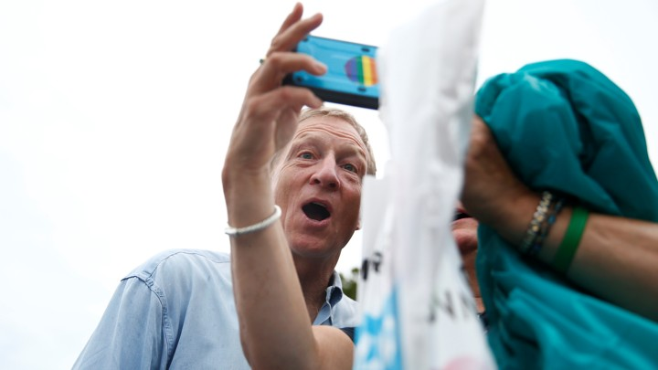 Tom Steyer makes a funny face while taking a selfie with a woman at the Iowa State Fair.