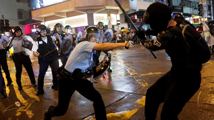 A police officer strikes a Hong Kong protester with a baton.