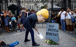 "A man wearing a Boris Johnson mask stands outside Downing Street, pretending to dig a grave for ""British Democracy."""