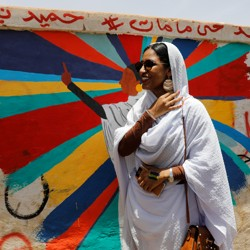Alaa Salah, dressed all in white, stands in front of a mural of herself.