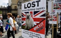 People walk past pro-Brexit placards in central London.