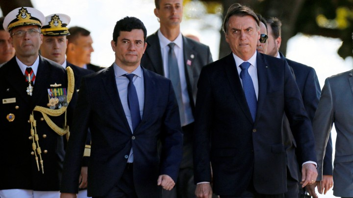 Sérgio Moro and Jair Bolsonaro walk with marines at a military ceremony.