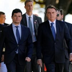 Sérgio Moro and Jair Bolsonaro walk with marines at a military ceremony.