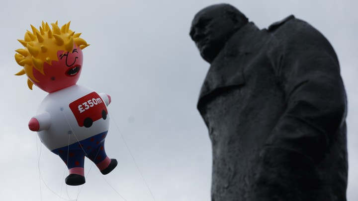 A giant inflatable blimp caricaturing Boris Johnson hovers beside a statue of Winston Churchill.