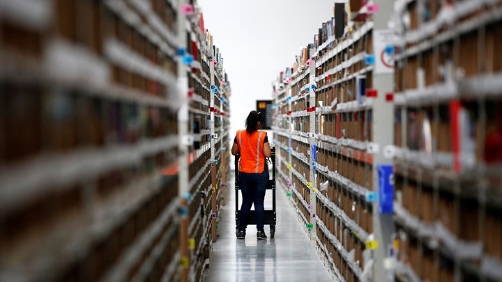 Employee looks for items in an Amazon warehouse