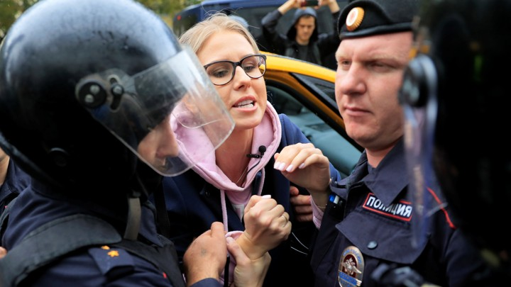 Law enforcement officers grab Lyubov Sobol's hands as she emerges from a taxi.