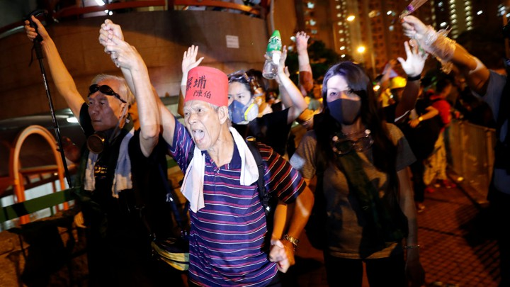 Protesters wearing gas masks and makeshift body armor march in the streets of Hong Kong.