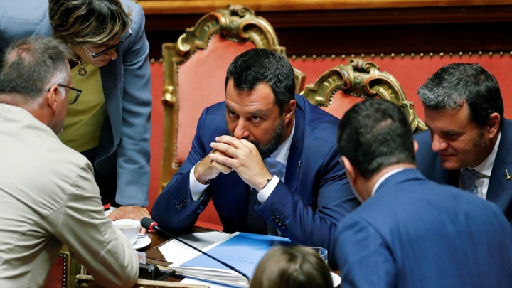 Matteo Salvini sits at a desk as he meets with other Italian lawmakers.