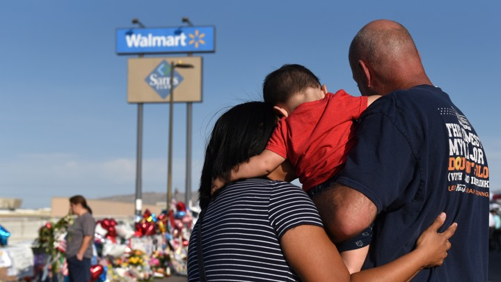 A man, woman, and child visit an impromptu memorial in El Paso.