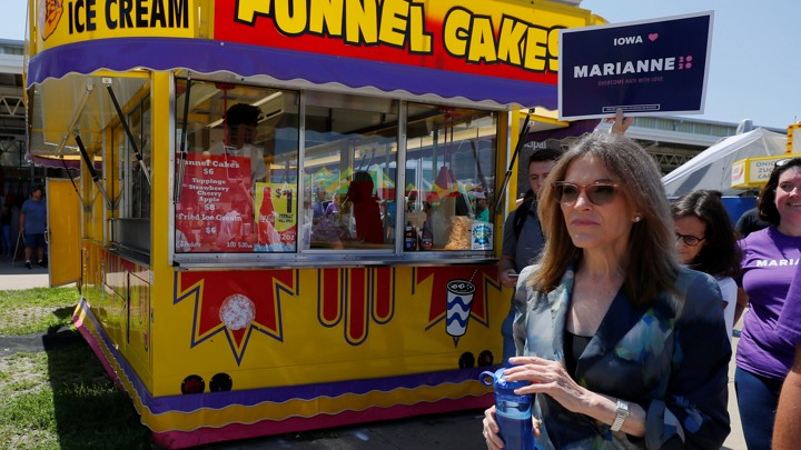 Marianne Williamson walks through the Iowa State Fair with a supporter holding a poster behind her as they walk in front of a funnel cake stand.