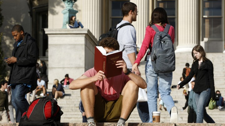 A person reads on a college campus