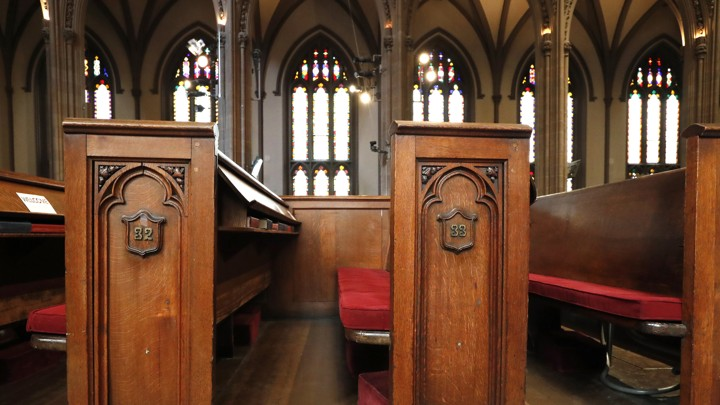 Empty church pews with stained glass in the background