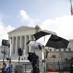 Television camera crews wait outside the Supreme Court