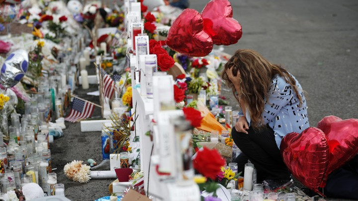 A woman crouches, head in hand, in front of a makeshift memorial near the scene of a mass shooting in El Paso, Texas. The memorial is made up of white crosses, prayer candles, American flags, and red heart-shaped balloons, among other items.