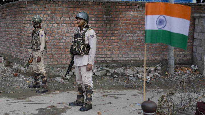 Indian paramilitary soldiers stand guard next to an Indian flag.