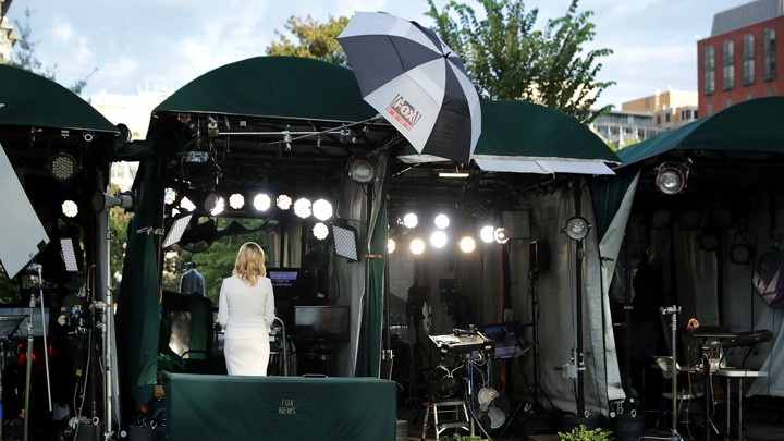 "A Fox News anchor, shot from behind, delivers a broadcast into the camera. She's standing on ""pebble beach,"" an area of the White House grounds where news networks set up their cameras for live shots."