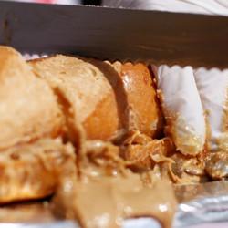 A knife cuts a long peanut-butter sandwich.