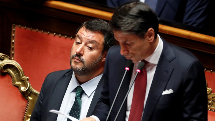 Matteo Salvini stares in dismay as Giuseppe Conte speaks at a podium.