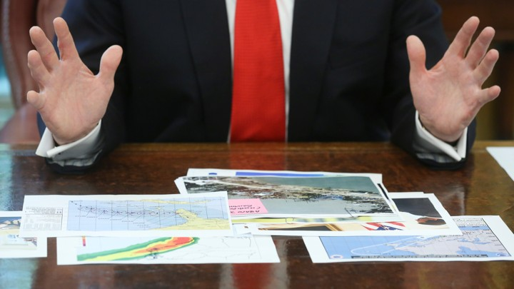 President Trump looks at hurricane-prediction documents.