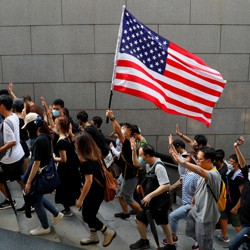 Hong Kong protestors hold up five fingers and brandish an American flag during a march.