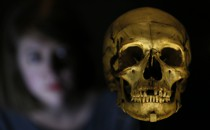 A woman looks at a human skull.