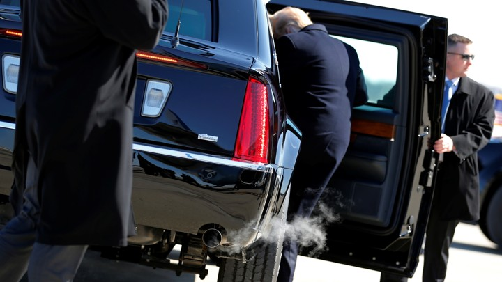 President Donald Trump climbs into a car held open by a secret service agent as exhaust comes out of the tailpipe.