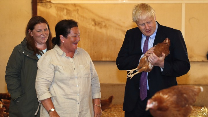 Boris Johnson holds a chicken in a barn beside two farmers.