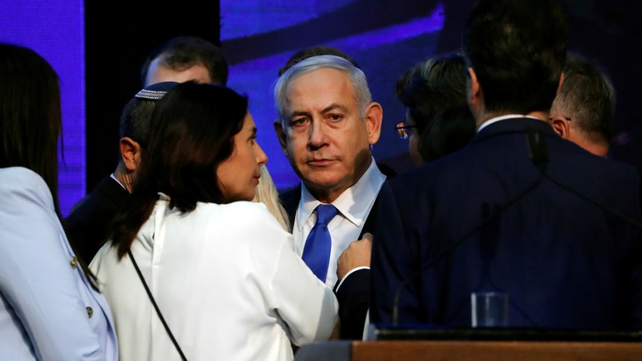A despondent-looking Benjamin Netanyahu is surrounded by party colleagues.