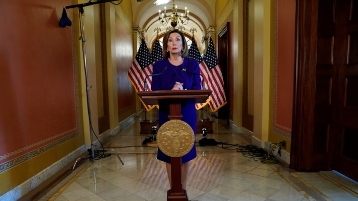 Nancy Pelosi stands in front of American flags and a lectern at the Capitol.