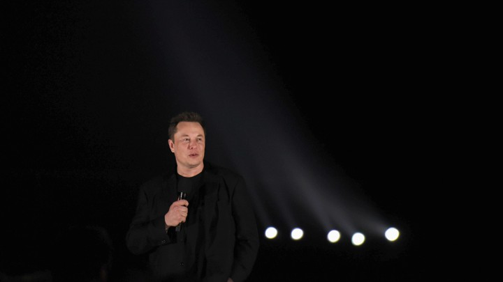 Elon Musk speaks into a microphone