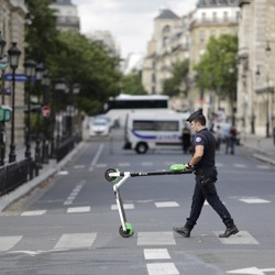 A police officer removes an electric scooter from the area around Notre-Dame cathedral in Paris.