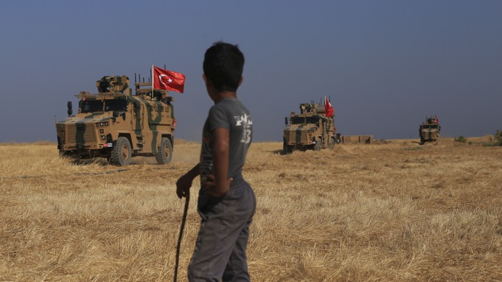 "Turkish armored vehicles conduct a joint ground patrol with American forces in the ""safe zone"" on the Syrian side of the border with Turkey"